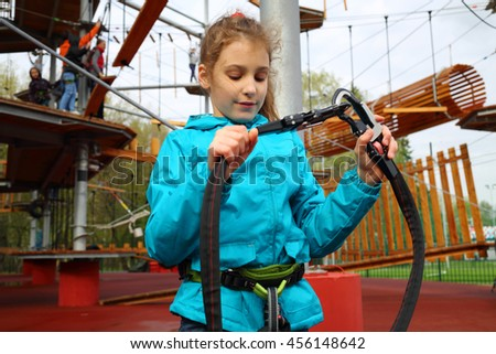 Happy pretty girl holds safety rope near Rope way on special playground - stock photo