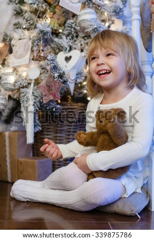 Happy pretty girl with toy bear sits near a Christmas tree in the room. - stock photo