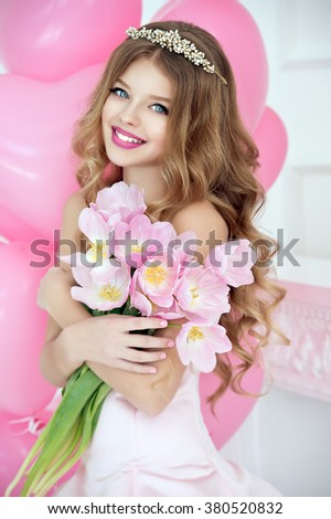 Happy pretty girl with tulips and pink balloons smiling and laughing at birthday party.  - stock photo