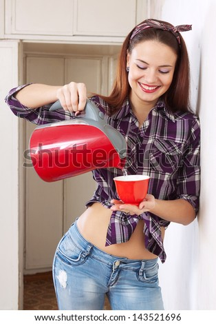happy pretty housewife girl pours water from the kettle into cup - stock photo