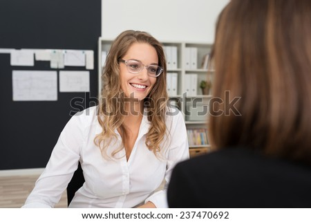 Happy Pretty Office Woman with Blond Hair, Wearing White Long Sleeve Shirt and Eyeglasses, Talking to Office-mate at her Worktable Area. - stock photo