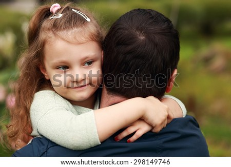 Happy pretty smiling kid girl hugging her father with love outdoor summer background - stock photo