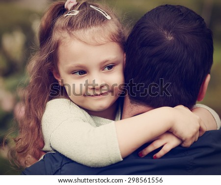 Happy pretty smiling kid girl hugging her father with love outdoor. Toned closeup color portrait - stock photo