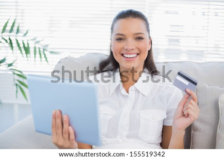 Happy pretty woman in bright living room buying online using her tablet pc