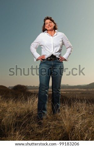 Happy pretty woman middle aged enjoying outdoors. Feeling free standing in grassy dune landscape. Clear sunny spring day with blue sky. - stock photo
