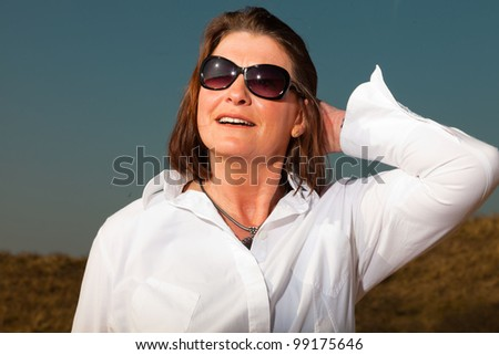 Happy pretty woman middle aged wearing sunglasses enjoying outdoors. Feeling free. Clear sunny spring day with blue sky. - stock photo