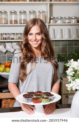 Happy pretty woman posing with homemade muffins - stock photo