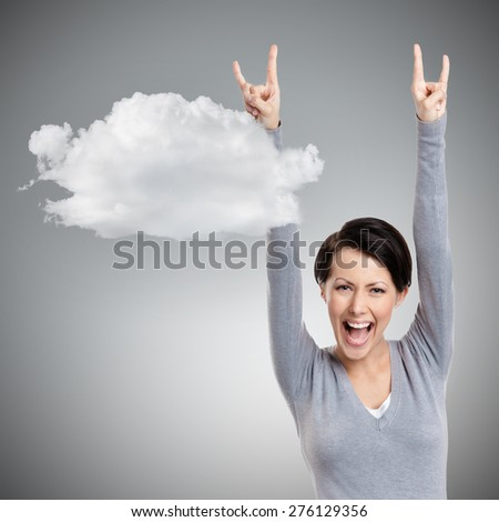 Happy pretty woman puts her hands up, isolated on grey background with cloud - stock photo