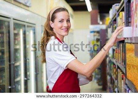 Happy pretty woman putting product on shelf at supermarket