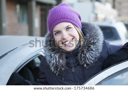 Happy pretty woman with an open car door in winter clothes - stock photo