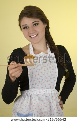 Happy pretty young girl wearing cooking apron over yellow background