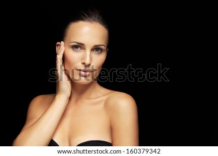 Happy pretty young woman model with beautiful skin. Lovely female holding hand by her face touching her healthy skin. Attractive young woman against black background - stock photo