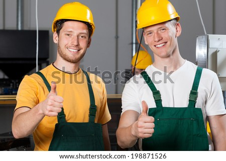 Happy production workers showing thumbs up sign - stock photo