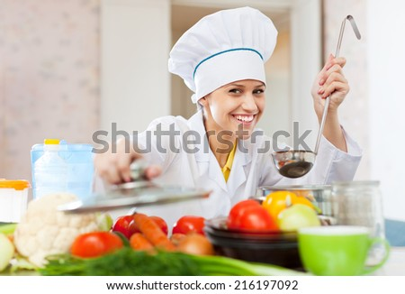 Happy professional cook in white workwear works in commercial kitchen - stock photo