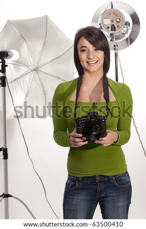 Happy professional photographer in her studio - stock photo