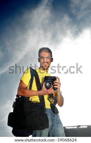 Happy professional photographer with camera outdoors over dramatic sky