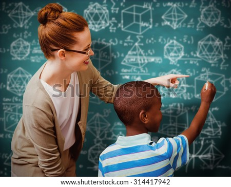 Happy pupil and teacher against green chalkboard - stock photo