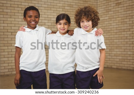 Happy pupils looking at the camera at the elementary school - stock photo
