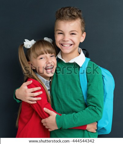 Happy pupils posing together in front of a big chalkboard. Back to school concept.  - stock photo