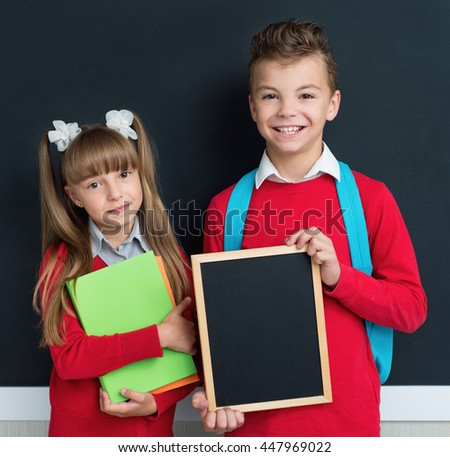Happy pupils posing together in front of a big chalkboard. Back to school concept.