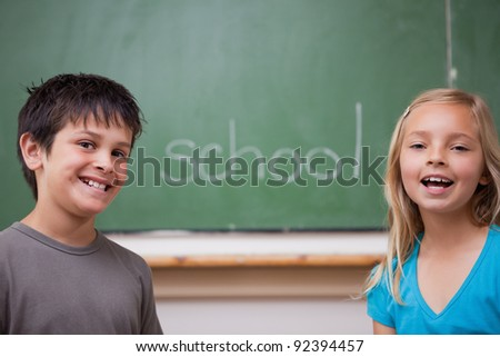 Happy pupils posing together in front of a chalkboard - stock photo
