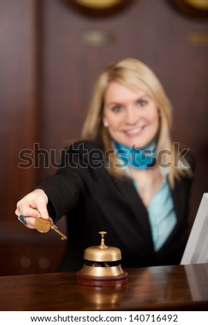 Happy Receptionist giving room keys to customer at reception in hotel - stock photo