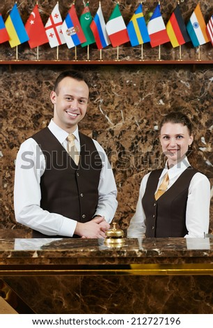 Happy receptionist workers standing at hotel counter - stock photo