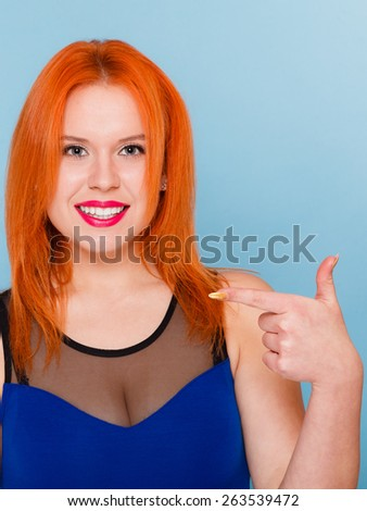 Happy red hair woman giving thumb up sign hand gesture and pointing isolated - stock photo
