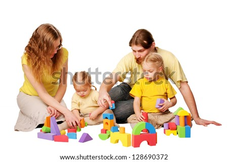 Happy red-haired father, mother and two children building from toy blocks. Family concept. Isolated on white background - stock photo