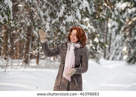 Happy red-haired woman having fun on winters day in forest.