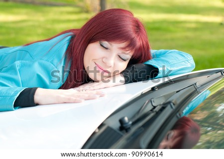 Happy red-haired young woman lying on the bonnet of her new car outdoors - stock photo