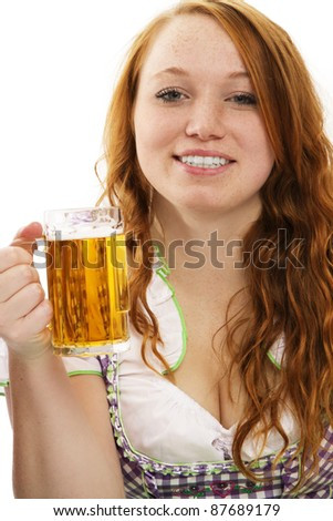 happy redhead woman in bavarian dress and a glass with beer on white background - stock photo