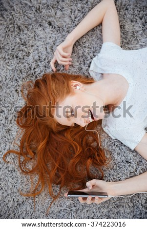 Happy redhead woman lying on the carpet and listening music on smartphone at home - stock photo