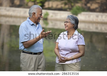 Happy relaxed couple talking in park - stock photo