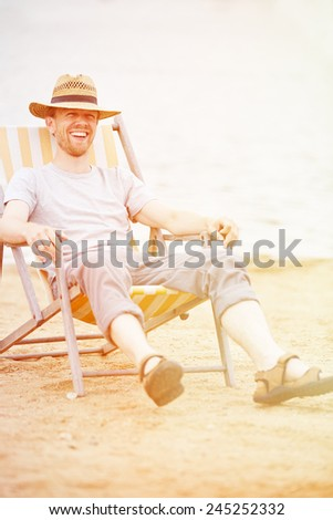 Happy relaxed Man sitting smiling in deck chair in summer on a beach - stock photo