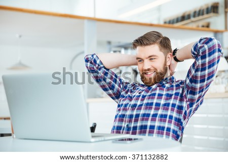 Happy relaxed man using laptop computer in coffee shop - stock photo