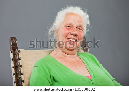 Happy relaxed senior woman with grey long hair sitting in chair. Studio shot isolated on grey background. - stock photo