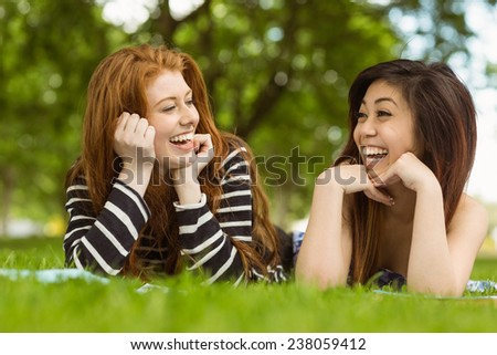 Happy relaxed young women lying on grass in the park - stock photo