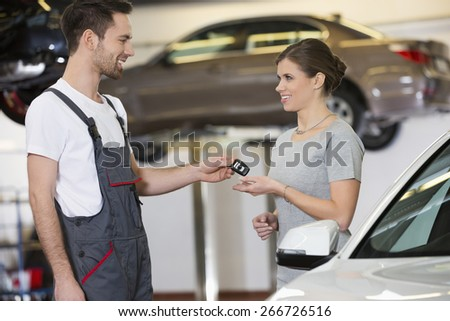 Happy repairman giving car key to woman in workshop - stock photo