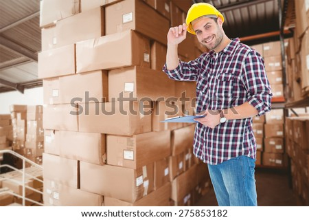 Happy repairman wearing hard hat while holding clipboard against shelves with boxes in warehouse - stock photo