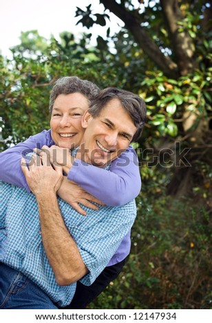 Happy retired couple hugging outdoors, closeup, looking at camera