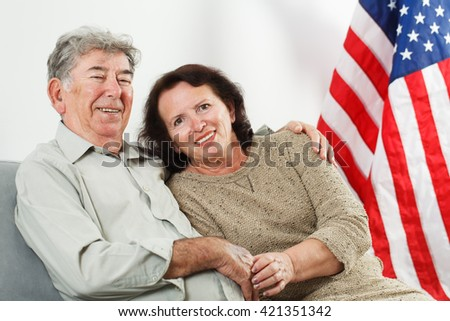 Happy retired couple on stars and stripes background