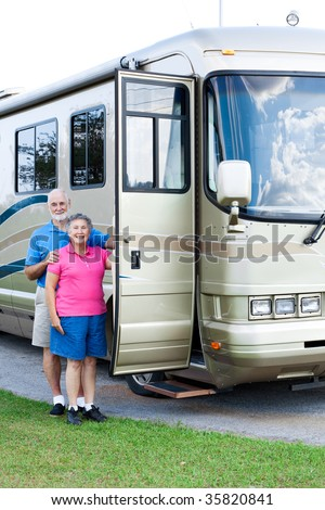 Happy retired couple standing beside their luxury motor home. - stock photo