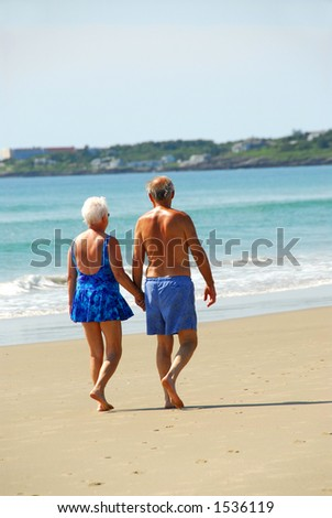 Happy retired couple taking a walk on a beach holding hands - stock photo