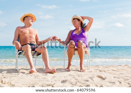 happy retired senior couple sitting on the beach holding hands and enjoying summer vacations - stock photo