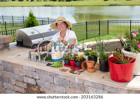 Happy retired senior woman filling the watering can with cold fresh water, while gardening and potting ornamental flowers, in a brick patio, in summer - stock photo
