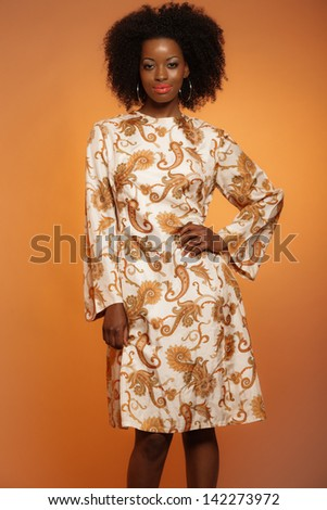 Happy retro seventies fashion african woman with paisley dress. Brown background.