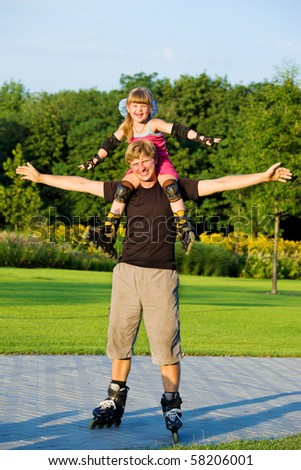 Happy rollerskaters - dad and daughter - stock photo