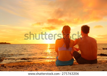 Happy Romantic Couple Enjoying Beautiful Sunset at the Beach Sitting in Sand looking at ocean sea and colorful yellow sky. - stock photo