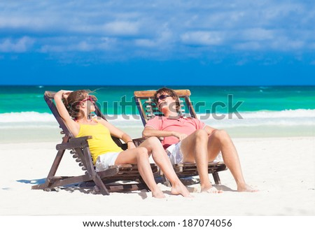 Happy Romantic Couple Enjoying the Sun at the Beach Looking at Each Other - stock photo